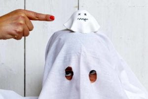 A child dressed as a ghost with a ghost cupcake on their head.