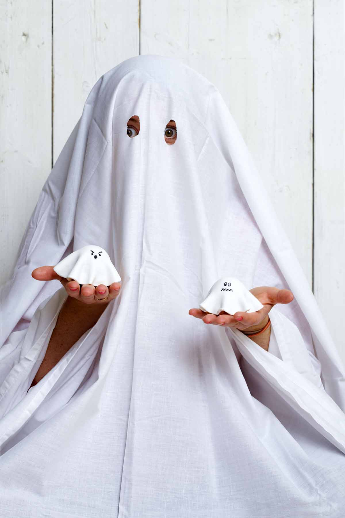 A child dressed as a ghost, holding a ghost cupcake in each hand.