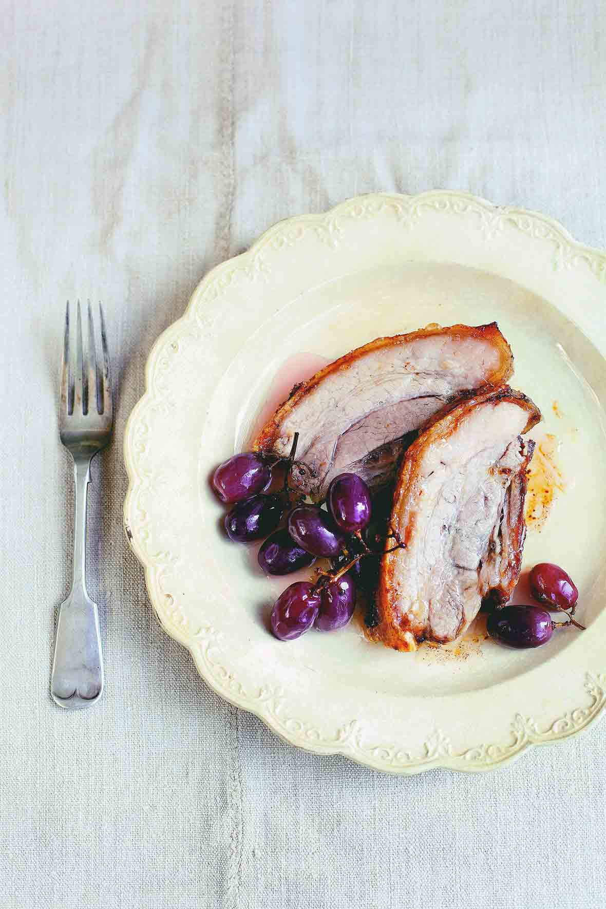A decorative plate with two slices of roast pork and three bunches of pickled grapes.