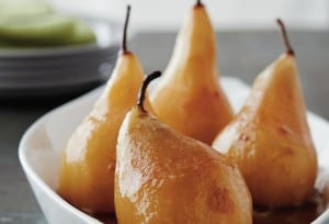 Four wine-poached pears in a white baking dish.