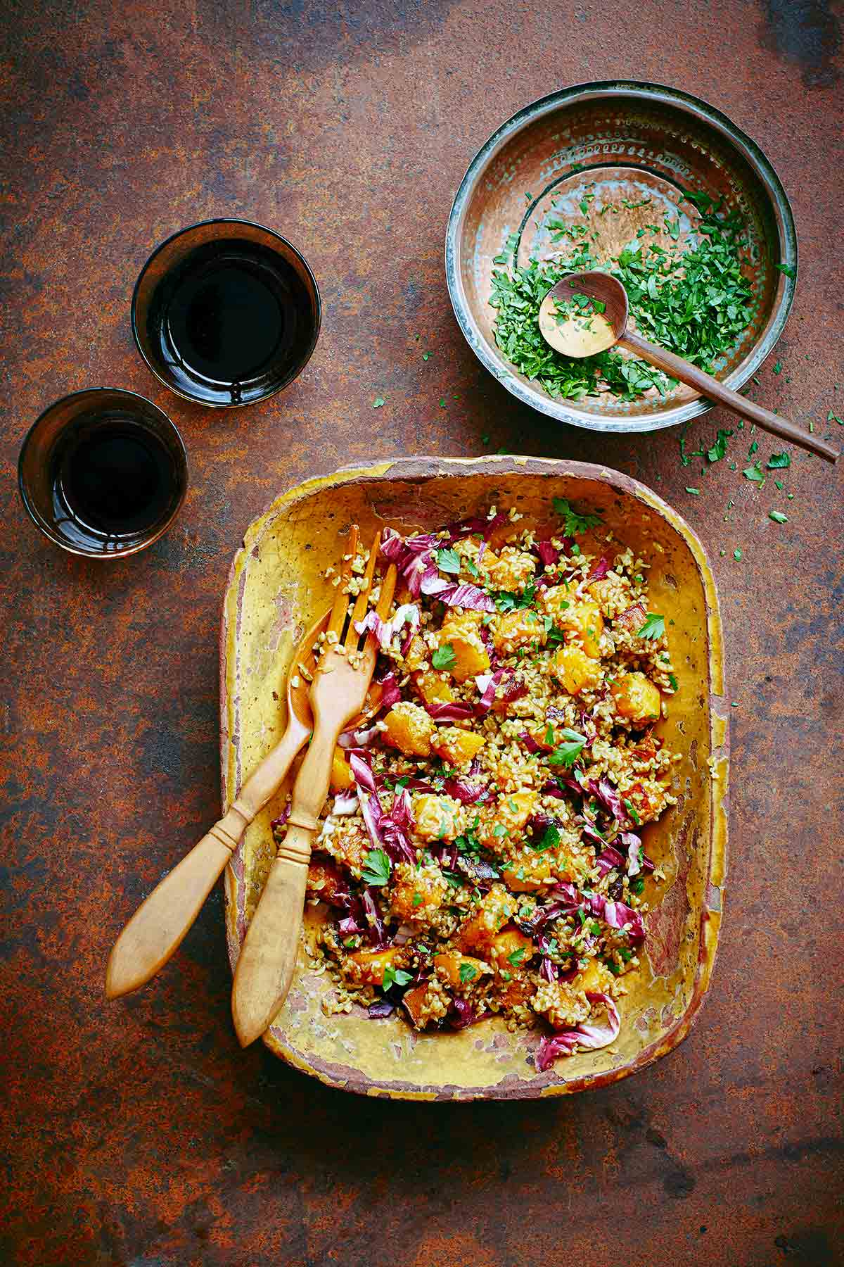 A wooden bowl with butternut squash and whole grain salad with a bowl of chopped parsley on the side and two glasses.