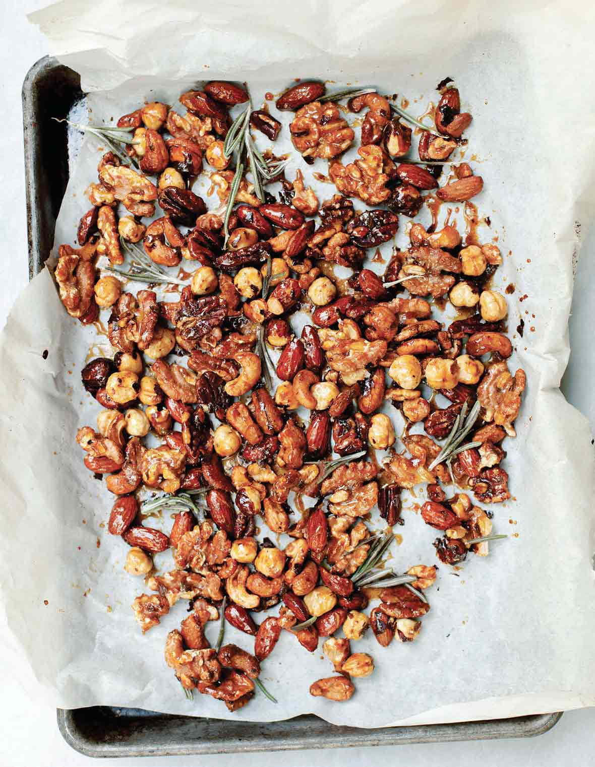 A layer of assorted nuts and rosemary sprigs on a sheet of parchment paper resting in a sheet pan