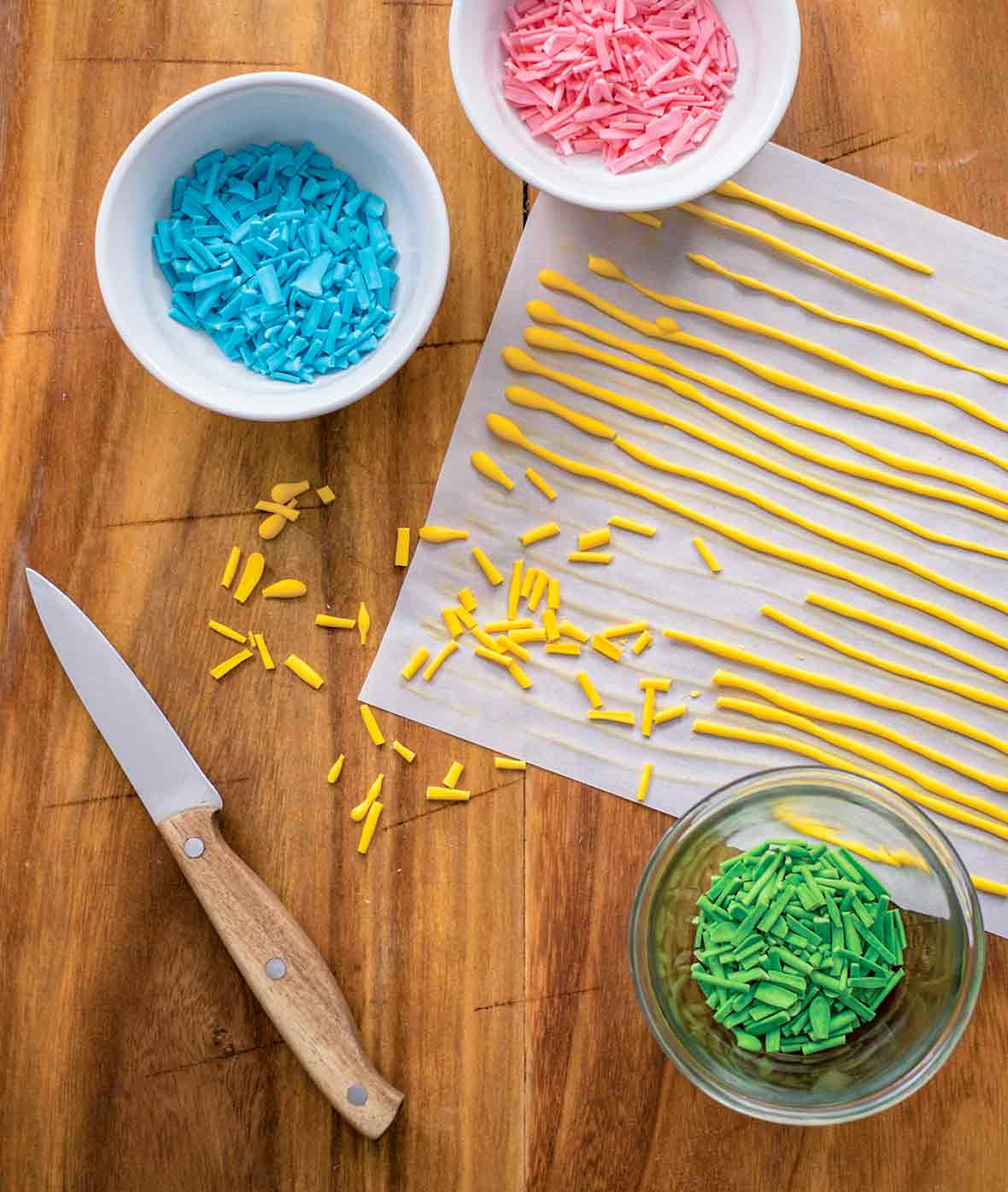 Parchment paper with long lines of yellow homemade sprinkles, plus bowls of green, blue, and pink sprinkles