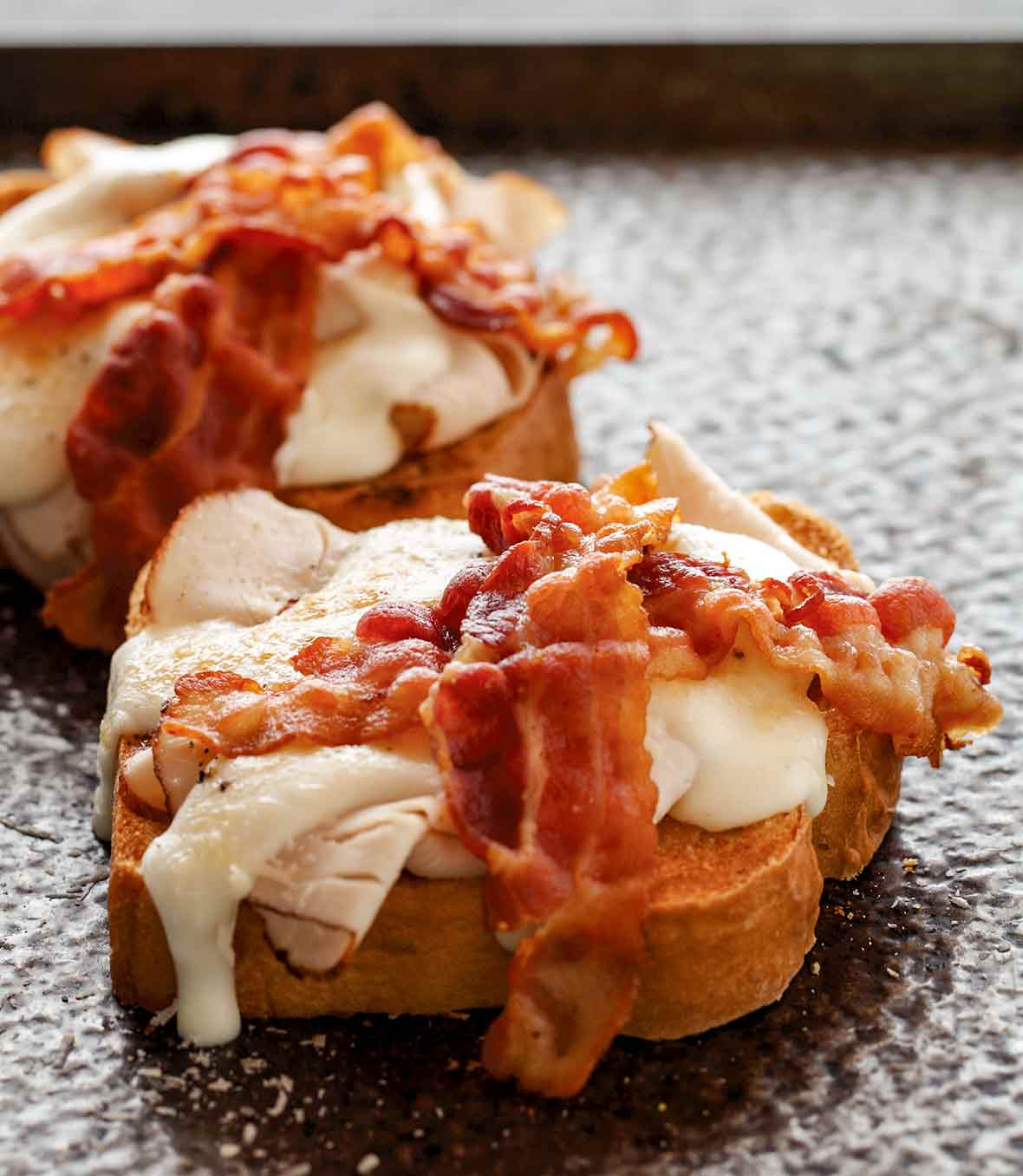 Two open-faced sandwiches topped with turkey, white sauce, and two slices of bacon