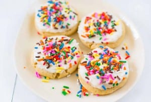 Four sugar cookies topped with frosting and sprinkles on a white plate.