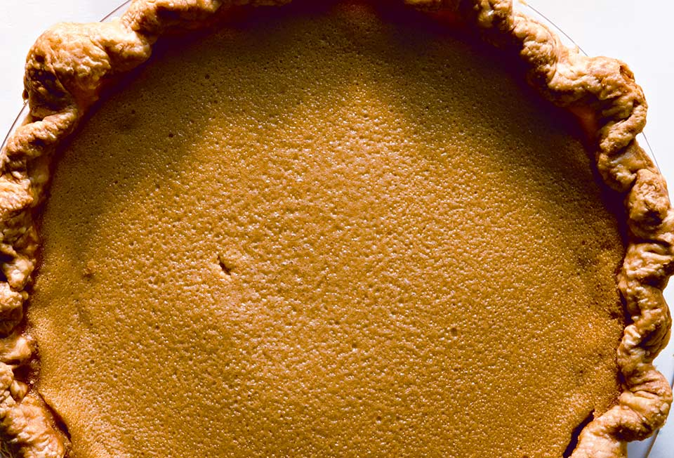 A whole cooked maple buttermilk pie in a glass pie dish.