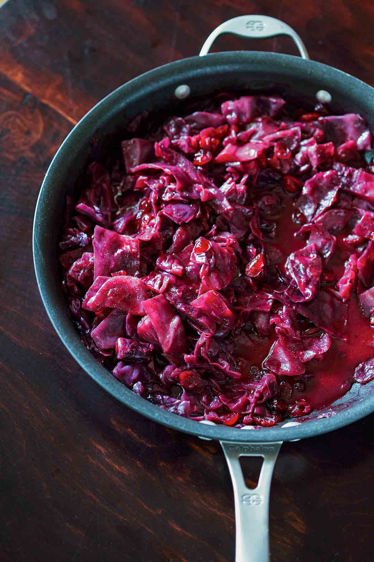 A Calphalon skillet filled with braised red cabbage with cranberries.