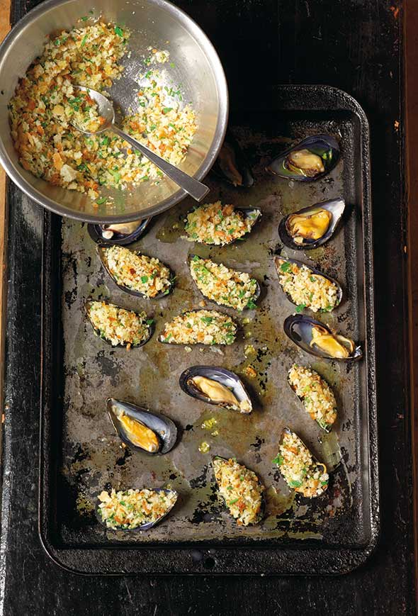 A rimmed baking sheet with stuffed broiled mussels and a bowl of filling on the side