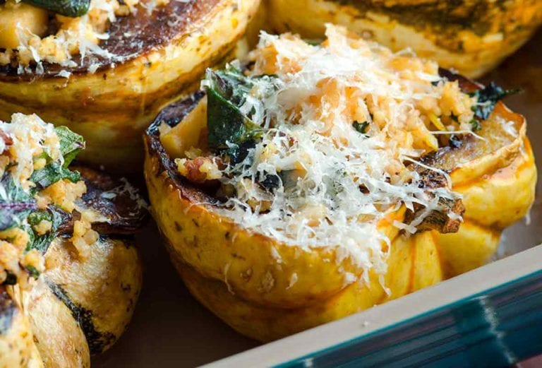 A casserole dish with four halves of roasted winter squash filled with cheese-topped stuffing