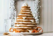 A stack of carrot cake pancakes layered with mascarpone frosting, shaped to look like a Christmas tree on a white plate.