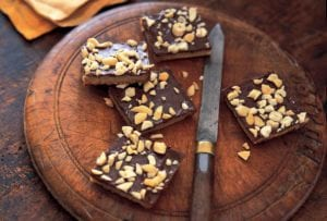 Four pieces of cashew caramel cracker bars on a round wooden board with a knife resting beside them.