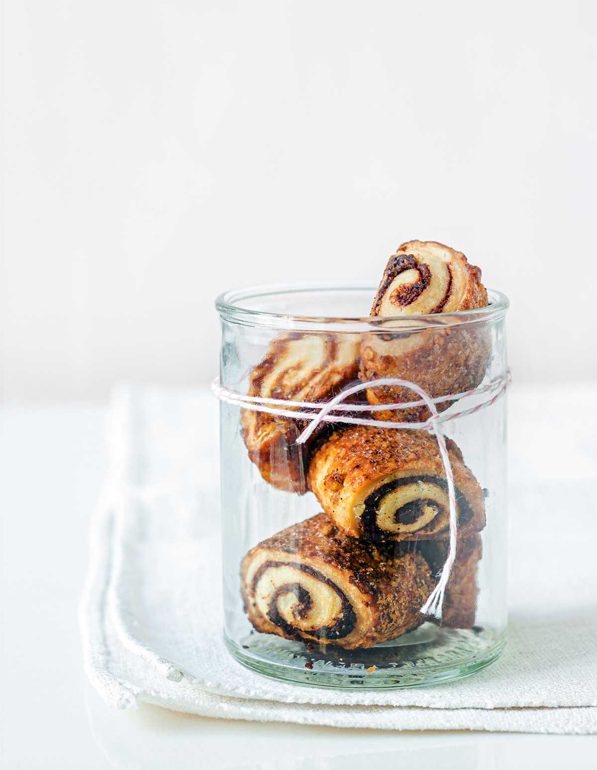Four cream cheese rugelach in a glass jar with twine wrapped around it.