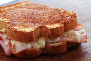 A grilled ham and cheese sandwich on a wooden cutting board.