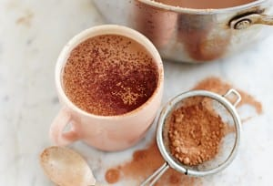 A pot and a mug filled with paleo hot cocoa and a sifter of cocoa powder on the side