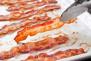 A white tray with slices of perfect baked bacon.