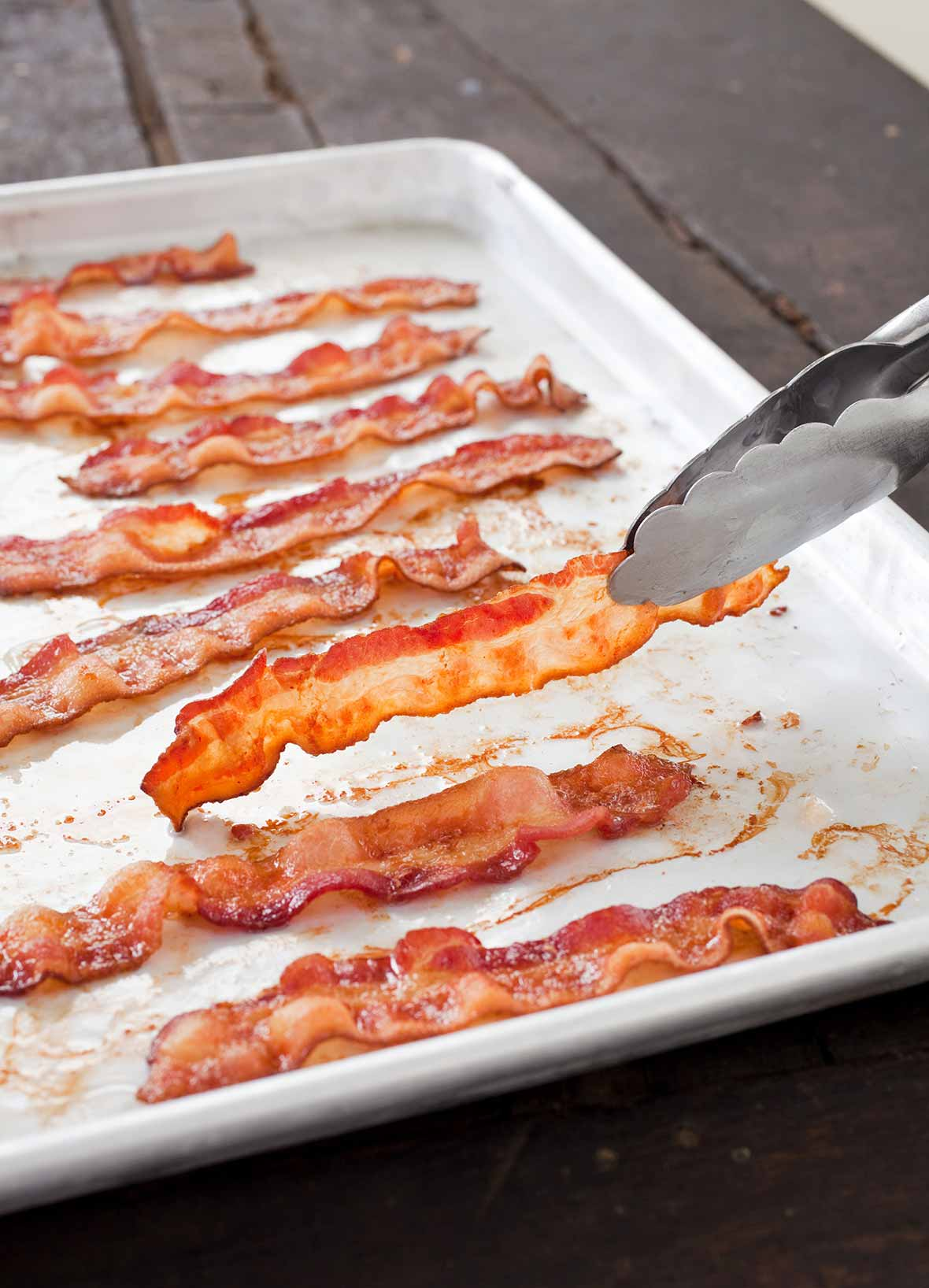 A white tray with slices of perfect baked bacon