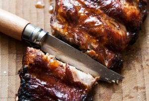A slab of glazed ribs with a knife cutting between two ribs