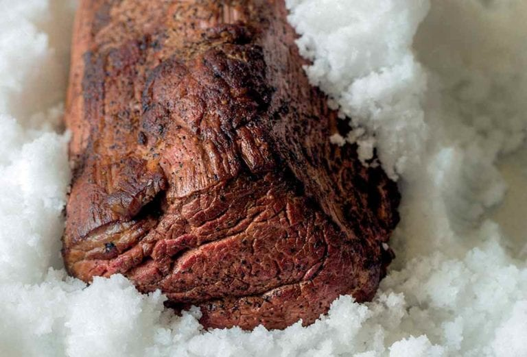 A cooked medium-rare salt-crusted beef tenderloin sitting in a pan of salt