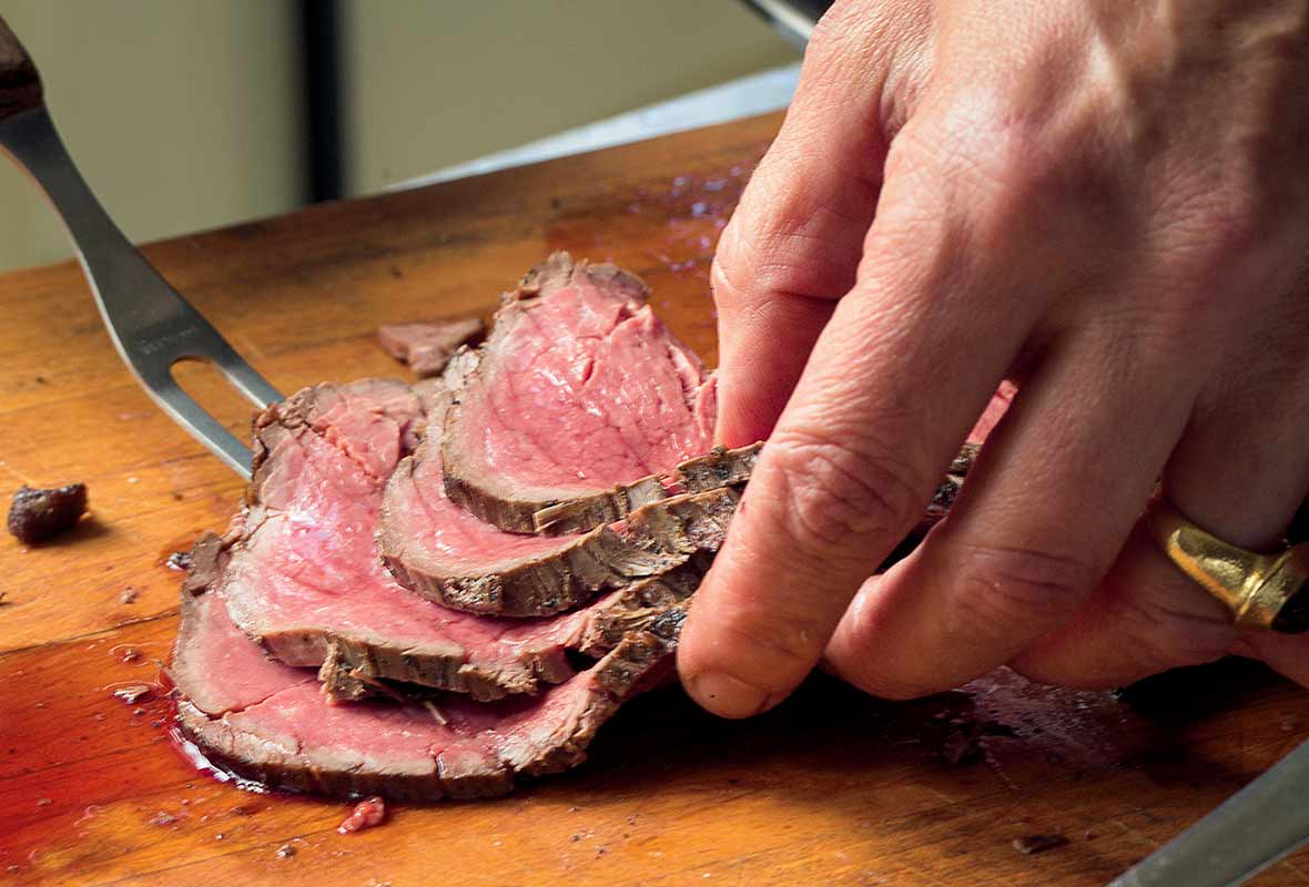 A medium-rare salt-crusted beef tenderloin being sliced on a cutting board