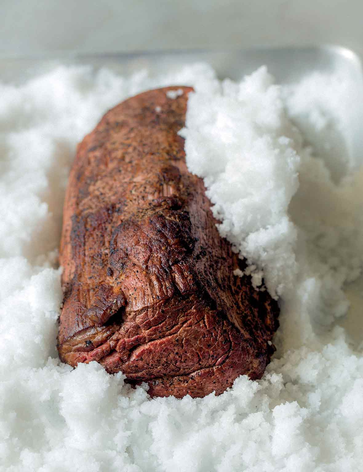 A cooked medium-rare salt-crusted beef tenderloin sitting in a pan of salt