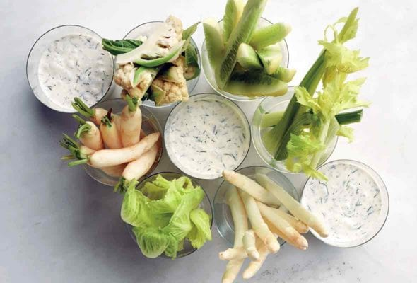 Three cups of buttermilk dressing with winter crudites in other cups.