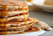 A stack of buckwheat pancakes drizzled with maple syrup on a white plate.