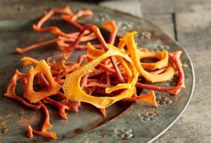 A pile of dried orange and lemon peels on a pewter plate
