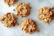 Five pistachio oatmeal cookies on a grey marble surface.