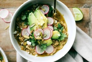 A white bowl filled with pozole verde, topped with sliced radishes, pepitas, avocado, and cilantro.