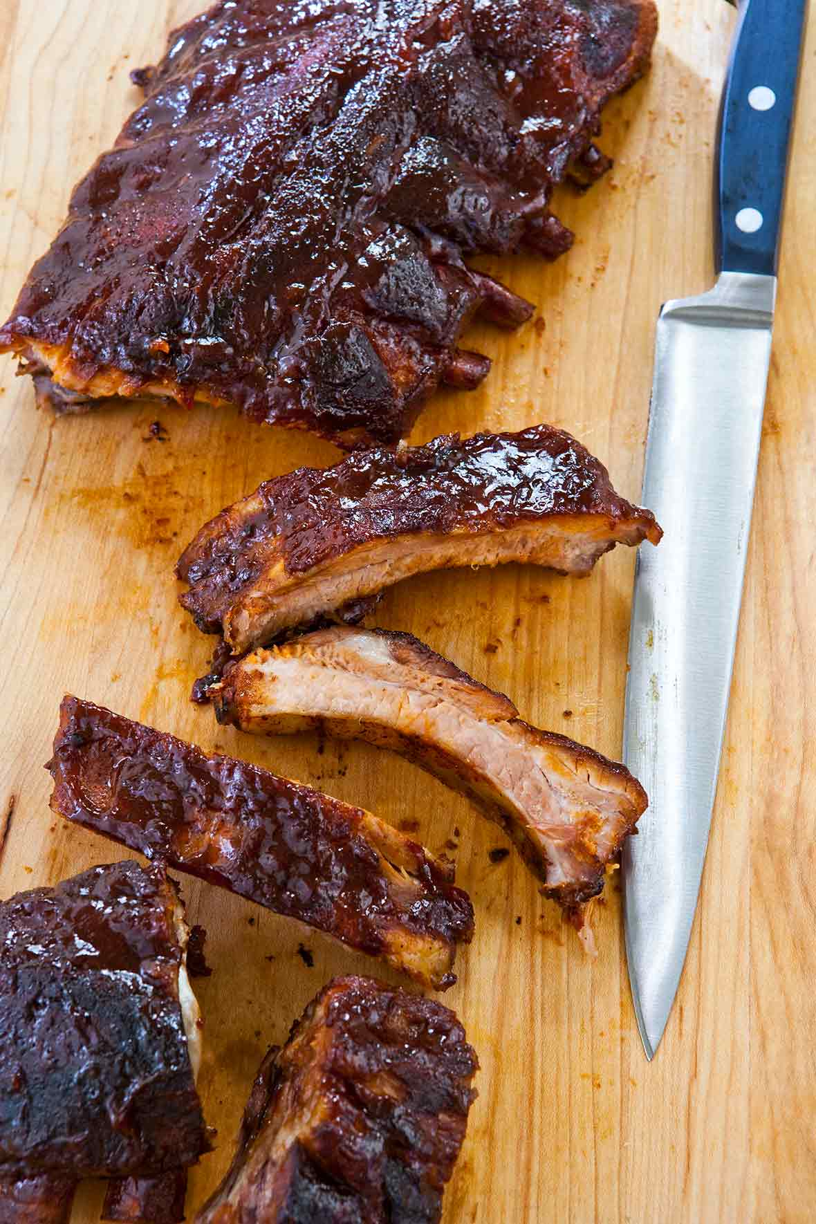A rack of slow cooker ribs on a cutting board with four single ribs cut off