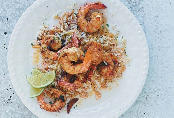 A white plate topped with sauteed shrimp, rice, and lime wedges.