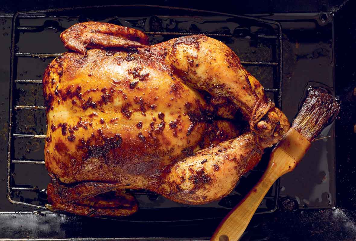 A whole spicy roast chicken on a rack set inside a baking dish with a brush lying beside the chicken.