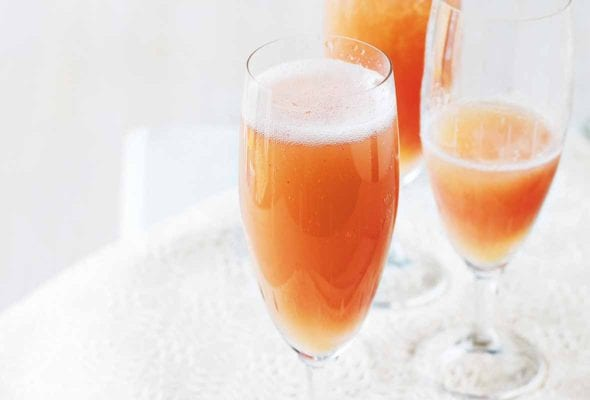 Three champagne flutes filled with classic bellini on a napkin.