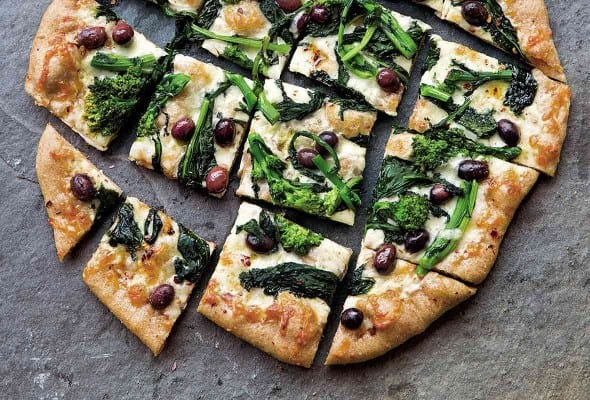 A broccoli rabe pizza cut into squares on a grey background.