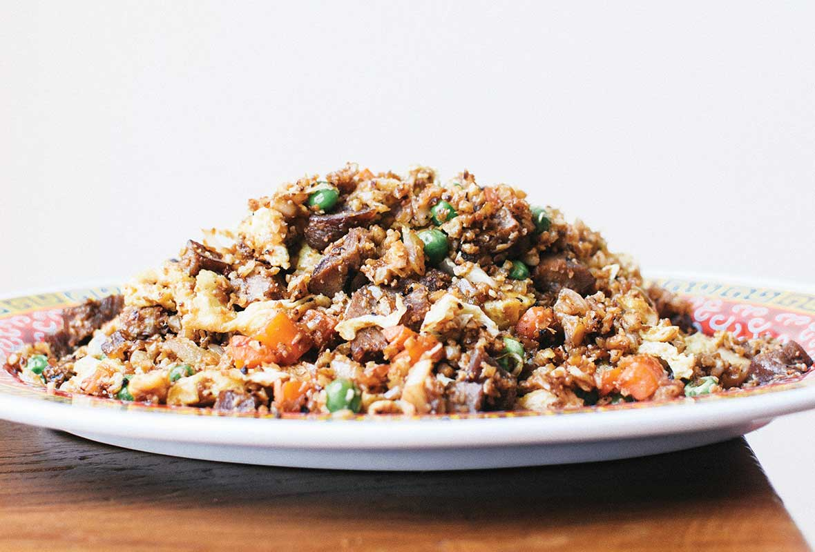 A plate mounded with cauliflower fried rice on a wooden table.
