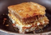 A cheese-crusted grilled cheese that is layered top and bottom with crispy Parmesan cheese in a skillet