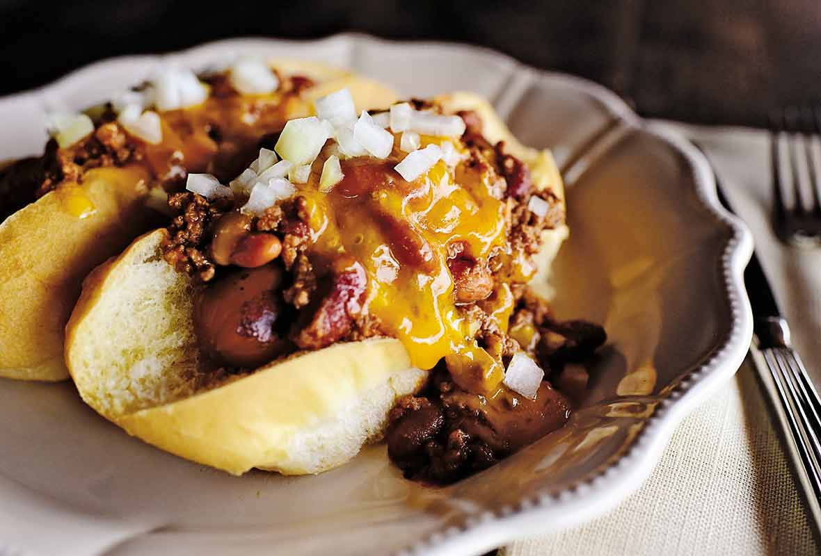 A decorative white plate topped with a chili dog in a white bun, covered in cheese and sprinkled with chopped onion.