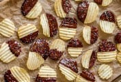 A layer of chocolate covered potato chips on a piece of parchment on a rimmed baking sheet.