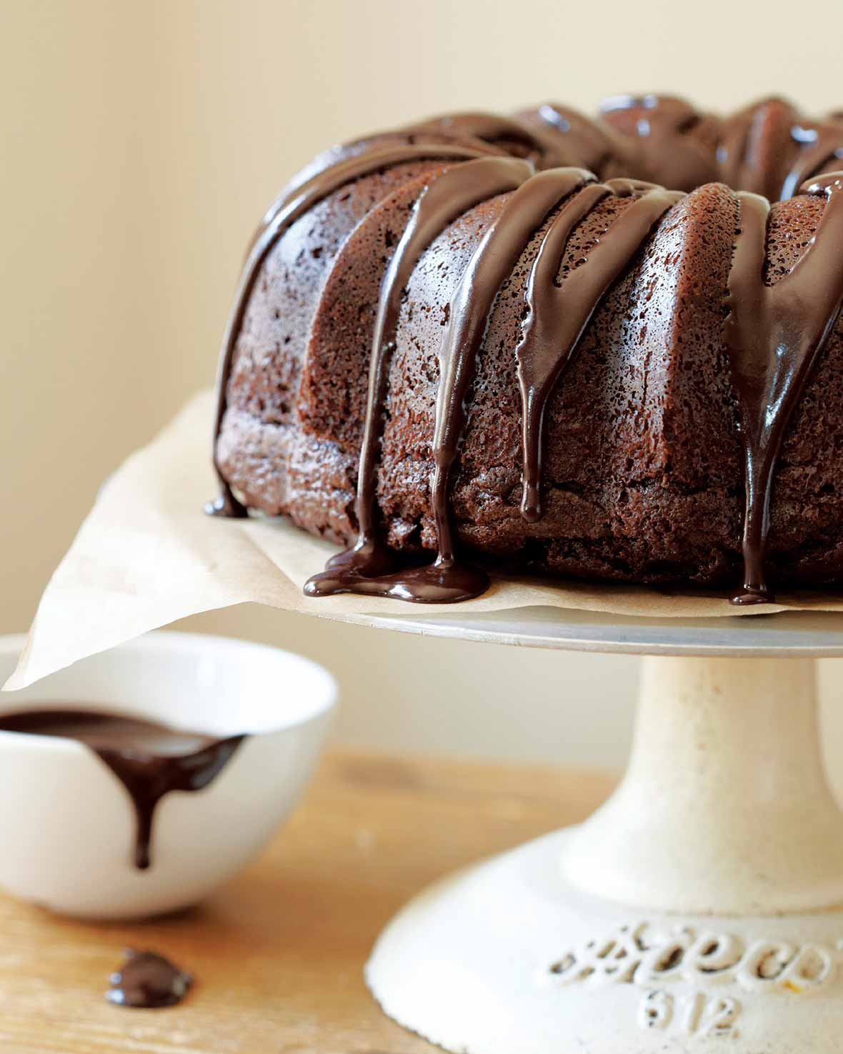 A chocolate glazed chocolate bundt cake sitting atop a white cake stand with a dish of glaze on the side