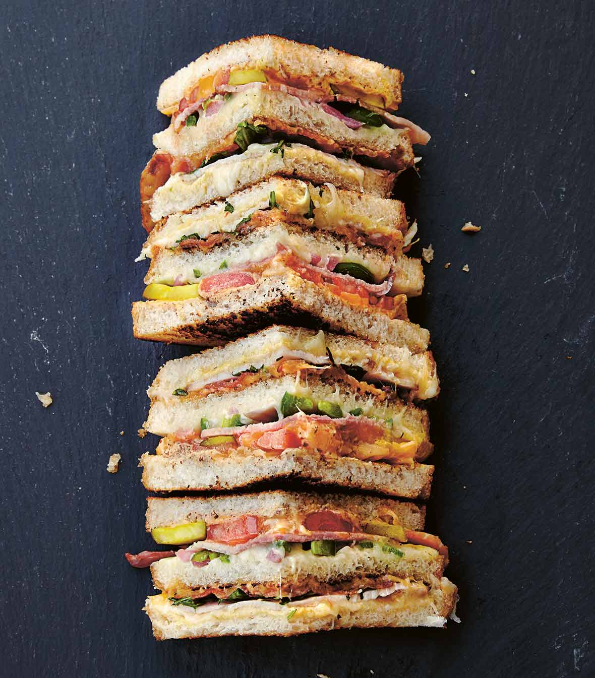 A grilled cheese with everything cut into four quarters.
