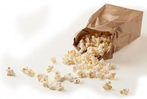 A brown paper bag with popped microwave popcorn spilling out of it.