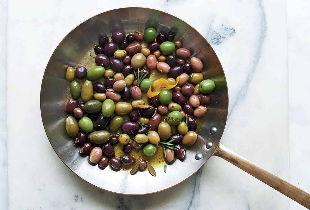 A metal skillet filled with warm olives, rosemary, and lemon zest.
