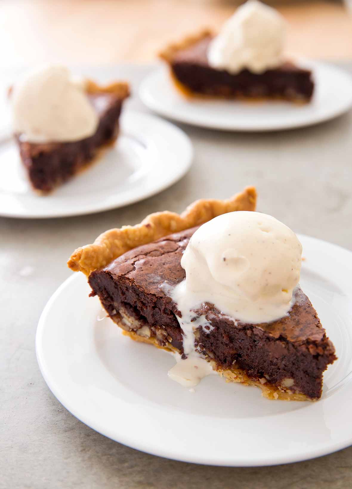 A slice of brownie tar heel pie on a white plate topped with a scoop of vanilla ice cream