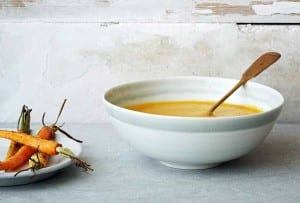 A white bowl filled with carrot ginger soup, with a spoon resting inside and a plate of carrots beside it.