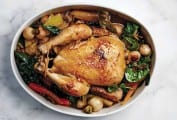 A whole chicken in a pot surrounded by vegetables including carrots, baby turnips, and spinach.