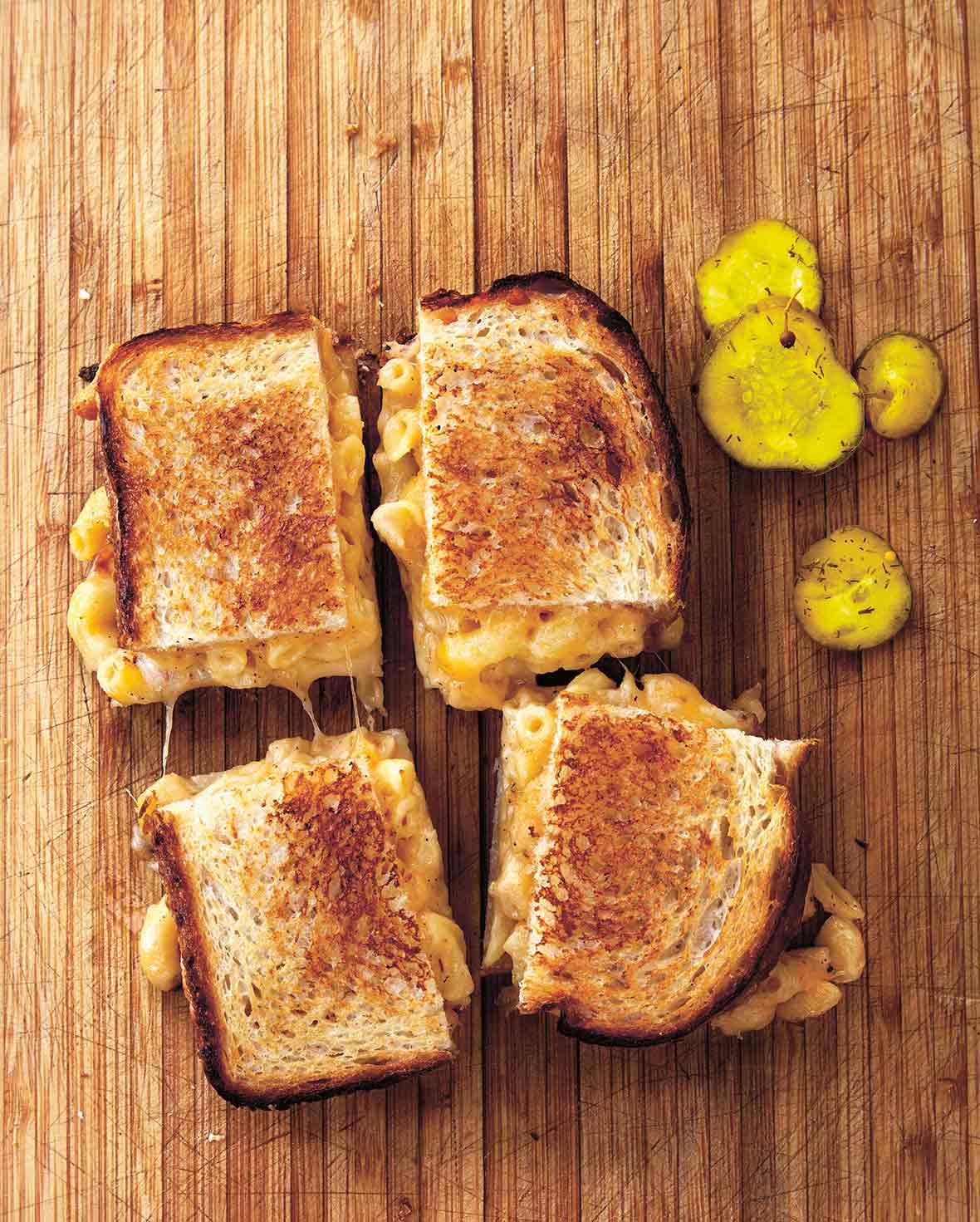 A grilled mac and cheese sandwich cut into four squares on a wooden board with pickle slices beside it.