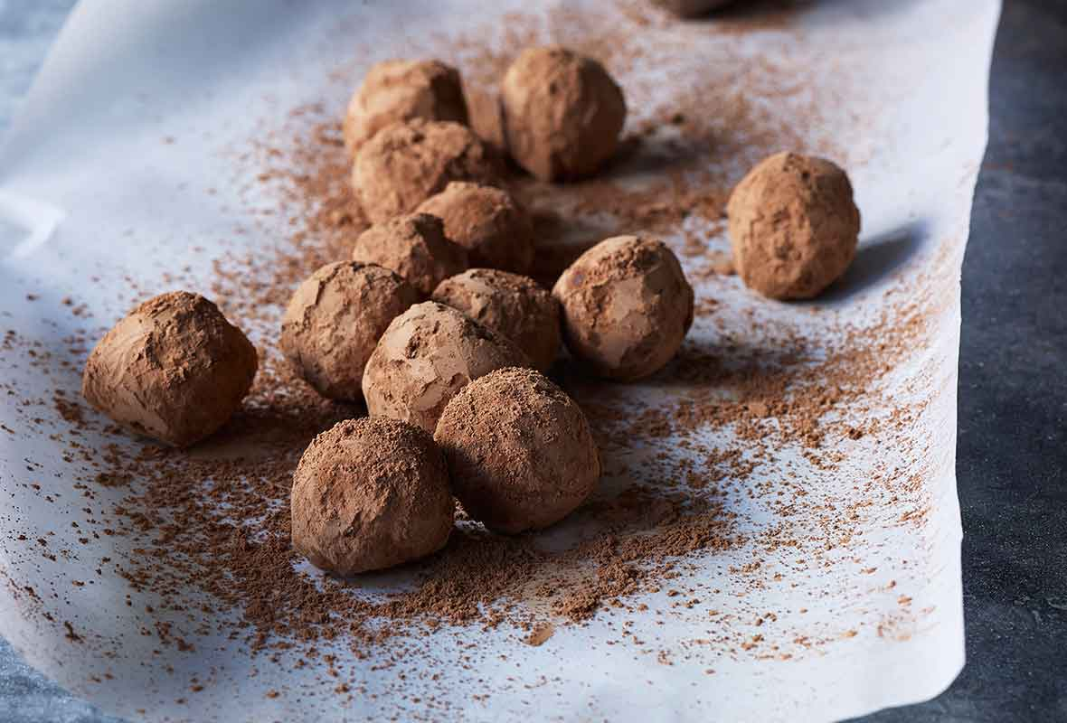 A sheet of parchment paper topped with chocolate truffles and a sifter of cocoa powder on the side