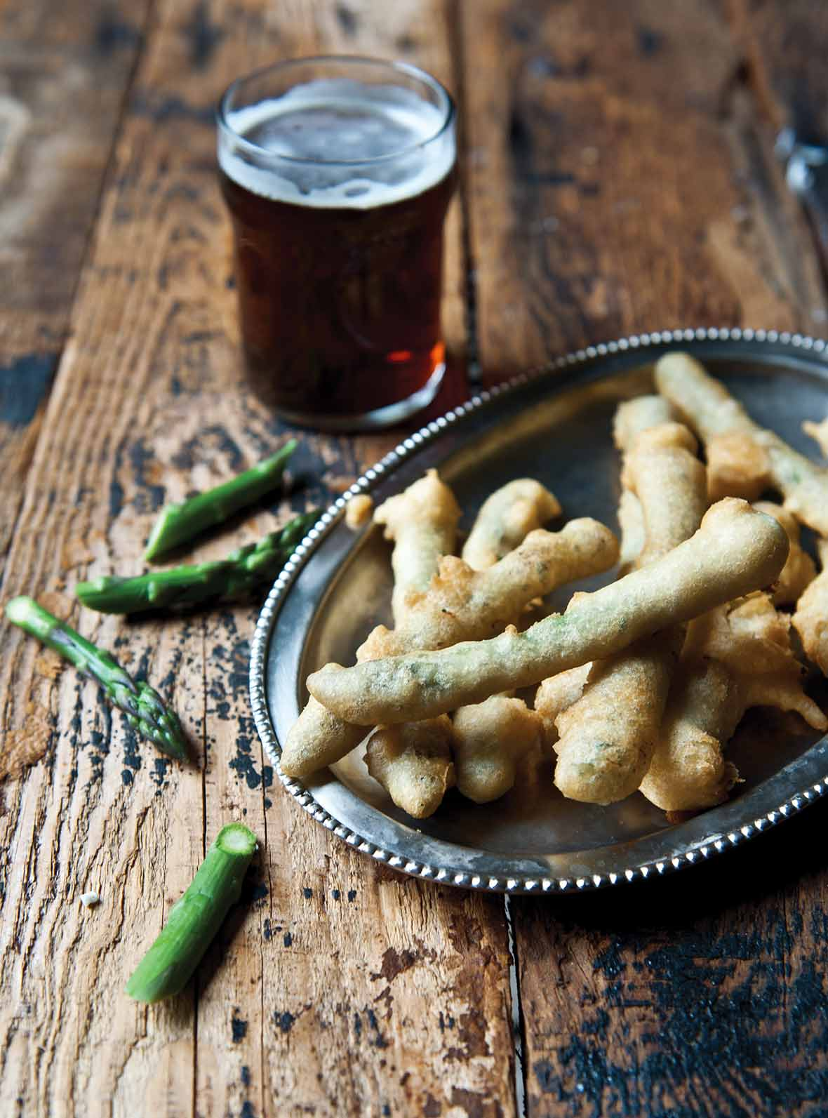 A silver platter filled with asparagus tempura with some pieces of asparagus and a glass of beer on a wooden table.