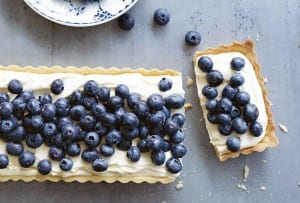A blueberry mascarpone tart with one slice cut off the end and a bowl filled with blueberries and a spoon resting in it.