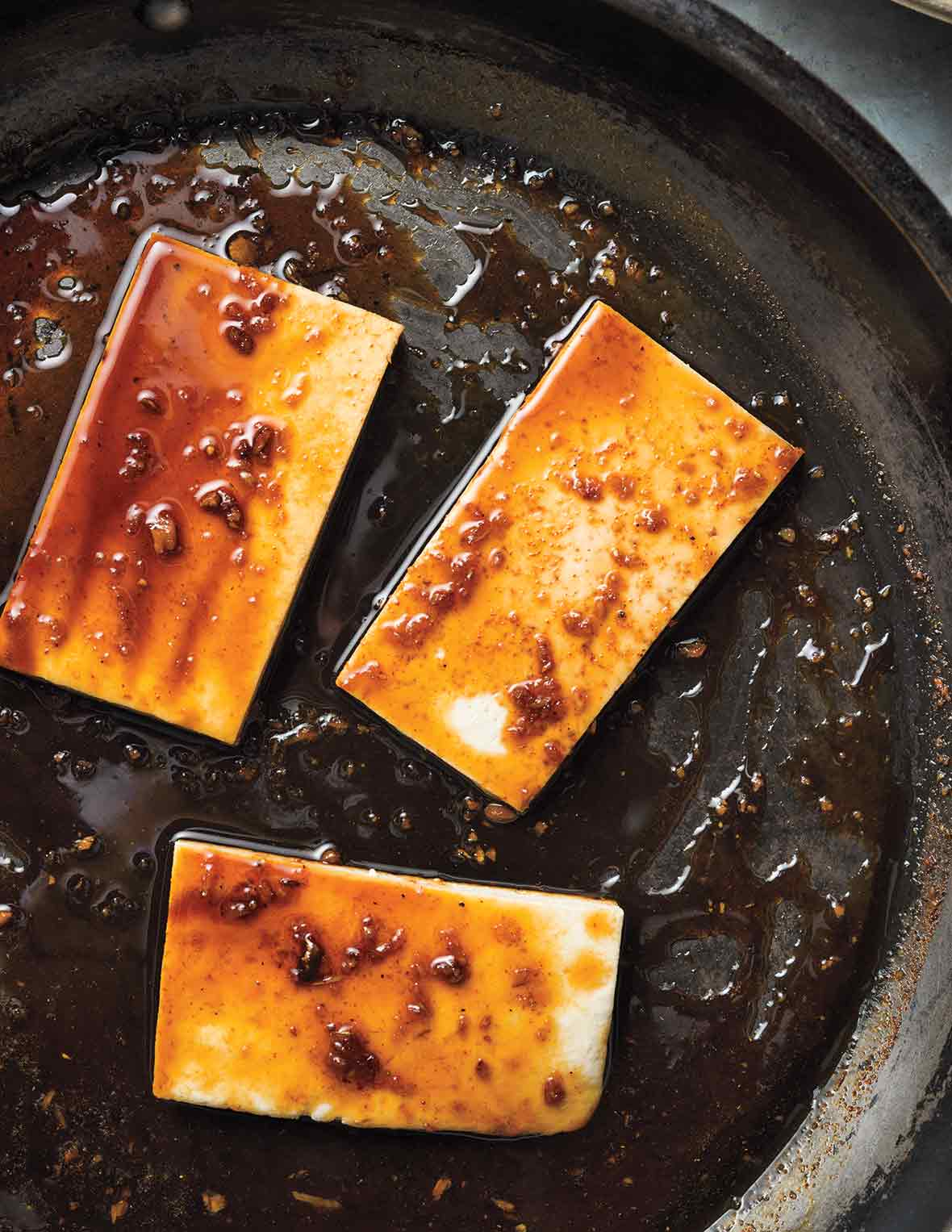 Three portions of glazed tofu in a skillet